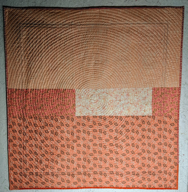 Four orange prints form the back of the quilt and the spiral quilting shows up beautifully here.