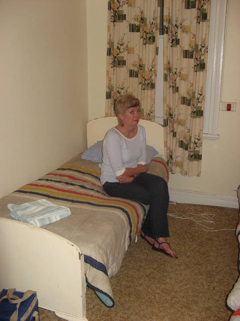 woman sitting on bed in a dingy hotel room looking not pleased