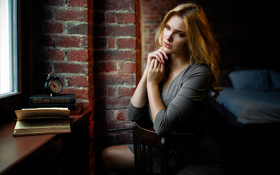 Chica rubia sentada en silla con un libro mirando por la ventana