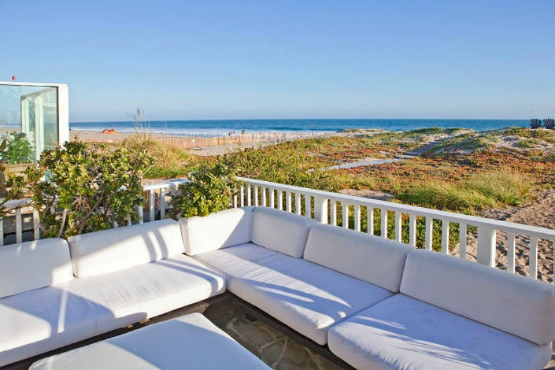 Coastal beach house balcony deck with lots of seating and ocean views