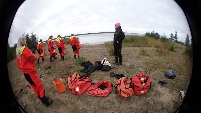 Varusteita rannalla, nuoret suuntaamassa mereen pelastautumispuvut päällä ja vesikiikarit kädessä.