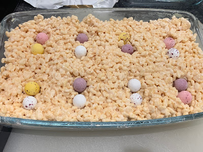 Marshmallow Crispy Treat mixture in a glass dish with mini eggs pressed into it