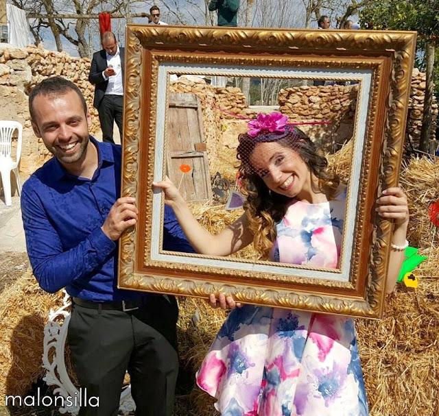Invitada a boda perfecta con vestido estampado corto con tocado tipo casquete con orquideas en el photocall al aire libre