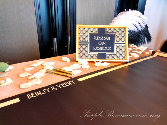 please sign our guestbook, gold pens, gatsby theme wedding, entrance arch, black, gold, hatten hotel melaka, backdrop, spotlight, decoration, decorator, elegant, 1920s, white feathers, metal lantern, glittered, pearls, B&Y initial block letters, gramophone