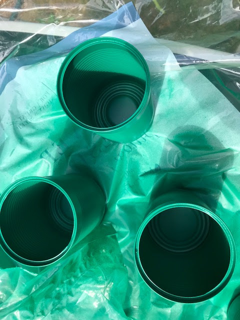 Cans on a plastic sheet, spray painted in green