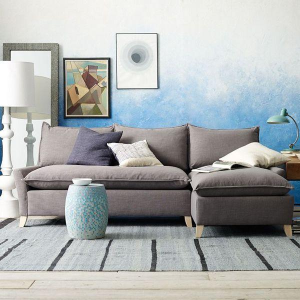 Sala de estar com sofá cinza e parede  ombré em tom de azul decorada com abajur de chão e luminária de mesa, almofadas cinza chumbo e branco, com dois quadros dispostos de forma harmônica na parede atrás do sofá