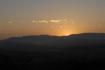sun peaking over tops of mountain range
