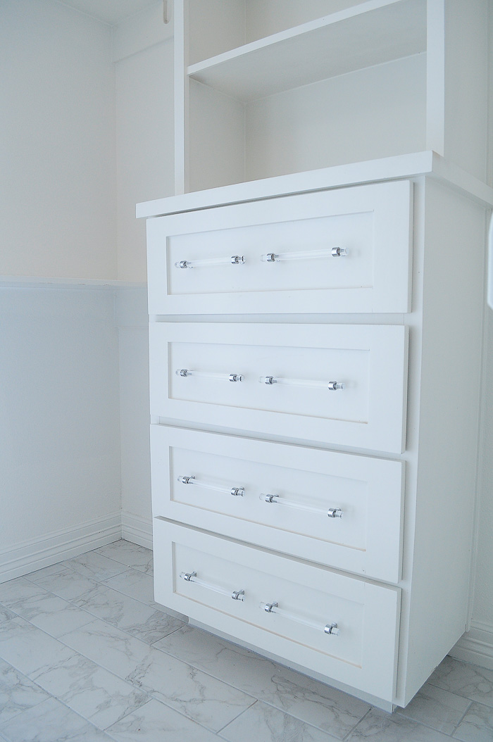 Master bedroom closet with white built-ins and lucite drawer pulls.