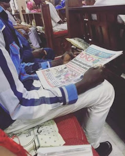 Man pictured reading newspaper during church service in Lagos