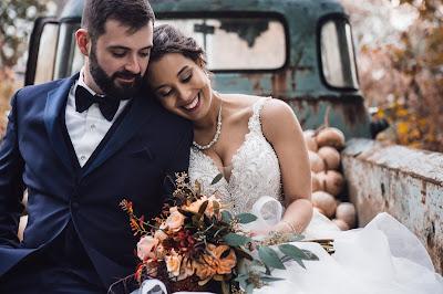 Pareja de novios en la parte trasera de una camioneta, posando felices el dia de la boda