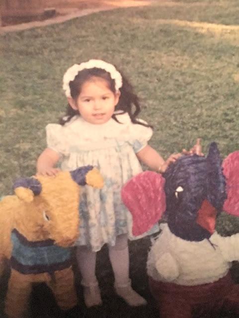 baby girl with long hair next to a pinata