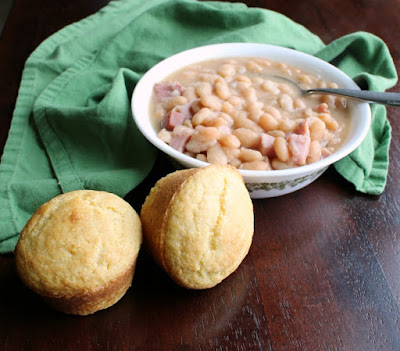 a couple of corn muffins next to a bowl of ham and beans
