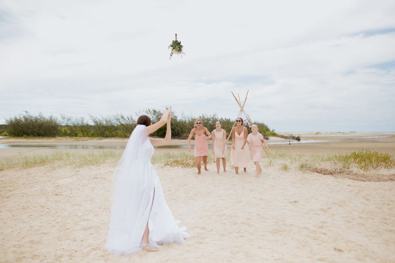 bride throws bouquet to bridesmaids