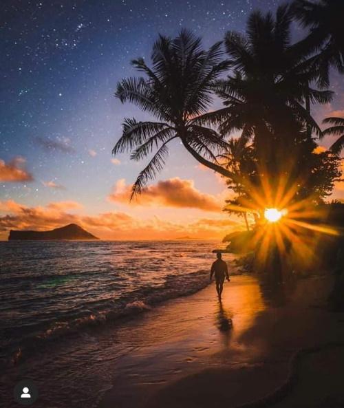 Linda paisagem do sol iluminando a água do mar e um jovem caminhando na areia.