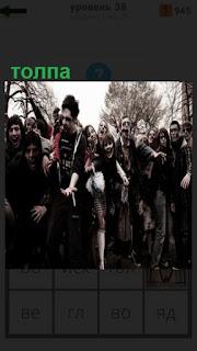 на улице собралась толпа молодежи  у которых лица разукрашены