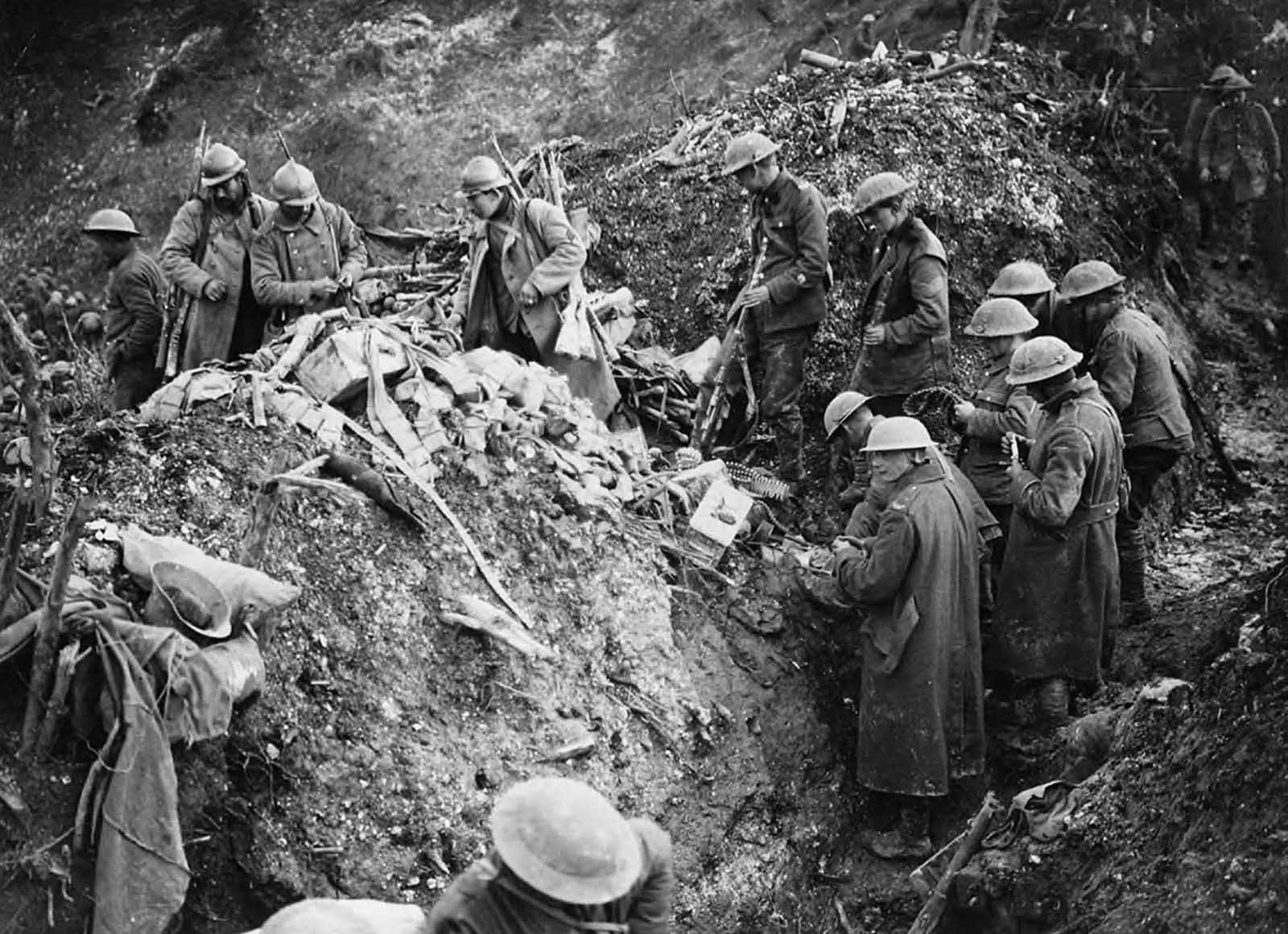 Cleaning up German trenches at St. Pierre Divion. In the foreground a group of British soldiers are sorting through equipment abandoned in the trenches by the Germans when St Pierre Divion was captured. One soldier has three rifles slung on his shoulder, another has two. Others are looking at machine gun ammunition. The probable photographer, John Warwick Brooke, has achieved considerable depth of field as many other soldiers can be seen in the background far along the trenches.
