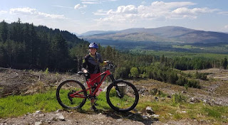 girl mountain biking with hiklls in background and trees