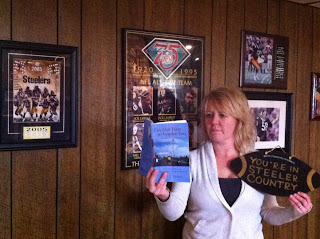 Bernadette Trillow holds the book up in front of Steelers memorabilia.