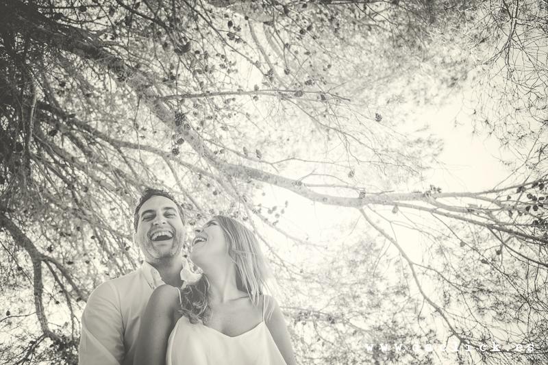 Oscar y Raquel ríen debajo de un árbol en la preboda