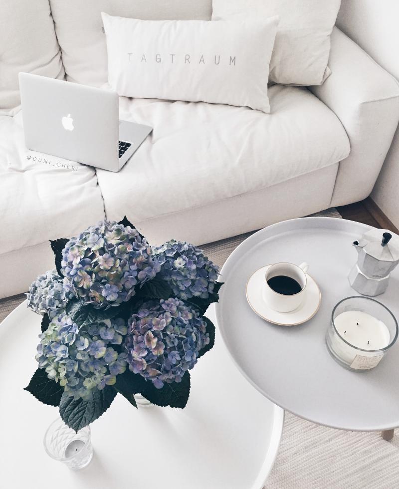 Weiße Couch mit blauen Hortensien Macbook und Kaffee