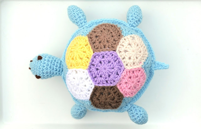 Top view of turtle displaying the 7 hexagons that make up the shell pattern.  With a lilac hexagon in the centre, clockwise from bottom: dark brown, white, yellow, tan, beige, pale pink. The turtle is facing towards the left.