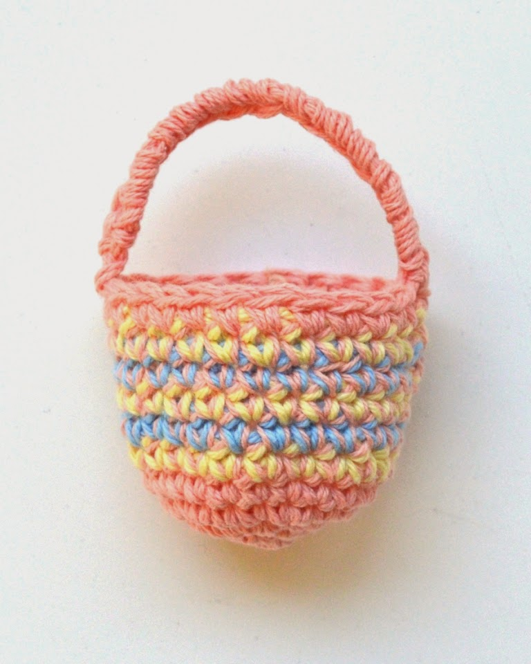 Mini crocheted basket with main colour solid apricot and one contrast section of 5 horizontal stripes yellow/apricot, blue/apricot, yellow/apricot, blue/apricot, yellow/apricot.