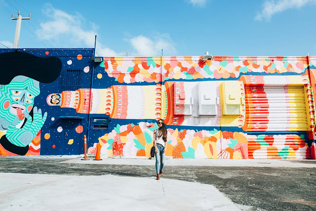 Photo of Drea Duclos in front of colorful wall