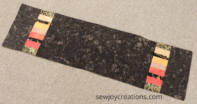 black batik runner with scrap strips