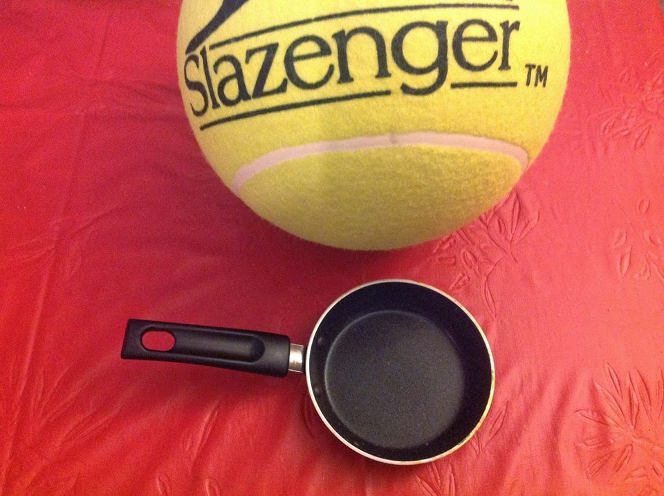 A giant tennis ball and tiny frying pan