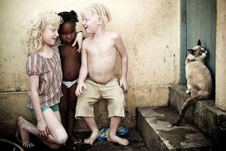 """O fotógrafo Alexandre Severo, um dos passageiros do acidente aéreo em Santos, é o autor do maravilhoso trabalho """"À Flor da Pele"""", em que retratou o dia-a-dia de irmãos albinos em uma família negra. Dos cinco irmãos, três sobrevivem fugindo da luz, procurando alegria no escuro.  Descrição: fotografia mostra três crianças próximas a uma parede encardida. A menor, uma garotinha negra está em pé entre os dois irmãos albinos, ela usa apenas a parte de baixo de um biquini branco; à esquerda, a irmã albina está ajoelhada, com o braço esquerdo abraça a irmã negra, ela usa uma blusa listrada em branco e marrom, short verde; à direita, o irmão albino está em pé com o peito desnudo e bermuda bege. Os três estão descalços. O casal albino estão sorrindo e direcionados à irmã negra que está séria e observa o chão. No chão molhado, atrás do pé esquerdo do garoto, há um saco azul de salgadinhos; à direita, próximo a eles há dois degraus, no segundo degrau há um gato encostado na porta."""