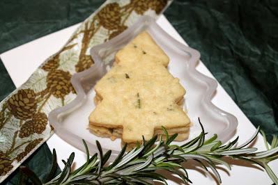 Baked rosemary shortbread Christmas tree shaped cookies on a small Christmas tree shaped dish with a rosemary garnish.