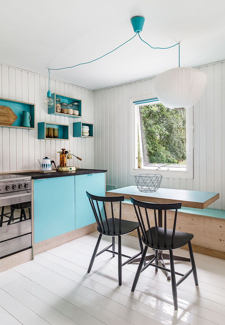Blue kitchen in scandinavian house, white floors and open box shelves