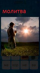 Мужчина на коленях молится в поле