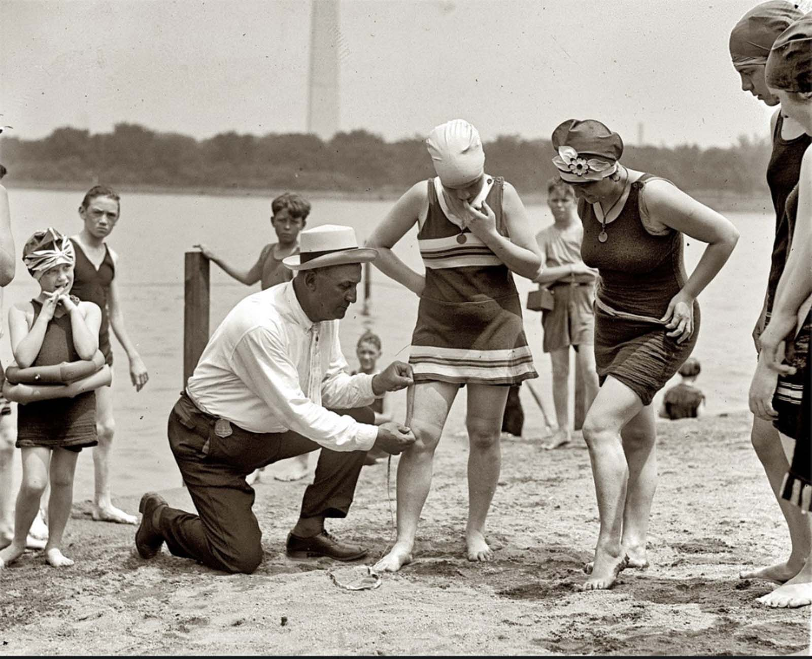 Washington policeman Bill Norton measuring the distance between knee and suit at the Tidal Basin bathing beach after Col. Sherrill, Superintendent of Public Buildings and Grounds, issued an order that suits not be over six inches above the knee. 1922.