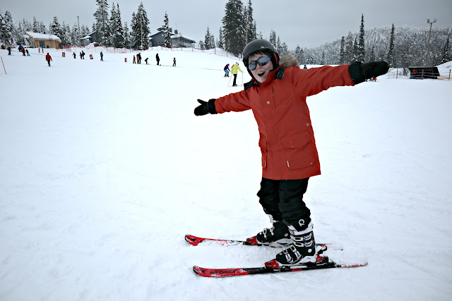 A boy in an orange ski jacket poses on skis with a back drop of rolling snow-covered ski slopes.