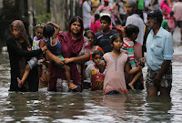 Sri Lankans wade through a road submerged in flood waters in Colombo, Sri Lanka, Tuesday, May 17, 2016. The Disaster Management Center said that 114 homes have been destroyed and more than 137,000 people have been evacuated to safe locations as heavy rains continue. (Credit: AP Photo/Eranga Jayawardena) Click to Enlarge.