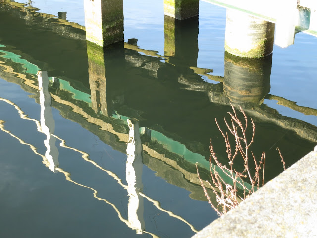 Posts supporting bridge with their reflections, reflection of bridge and handrail.