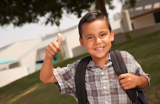 Boy wearing backpack and giving thumbs up