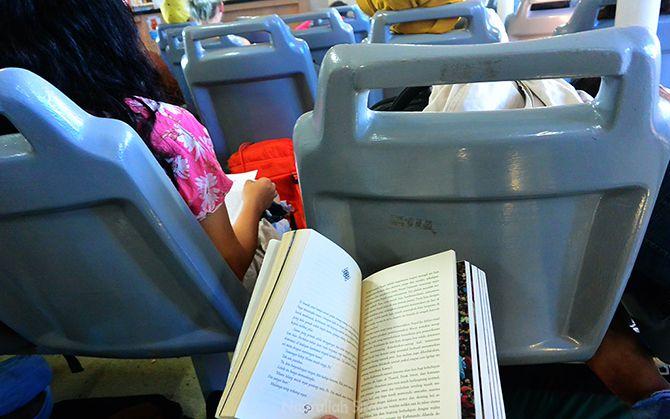 Membunuh waktu bosan dengan membaca buku di atas kapal