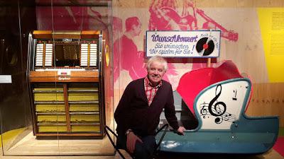 Mit einer Musikbox von 1957 und einer Chaise aus einer Kirmes-Raupen-Bahn von 1948 begann der Rundgang in der Essener Ausstellung auf Zollverein. Zur Erinnerung ließ sich Michael Winkler davor ablichten. (Foto: Werner Homann)