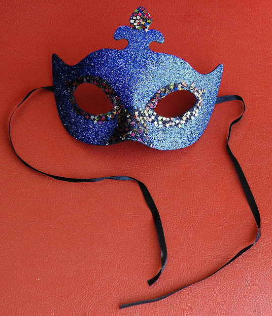A glittery blue mask with black ties, the type worn at a masquerade party or for Halloween.