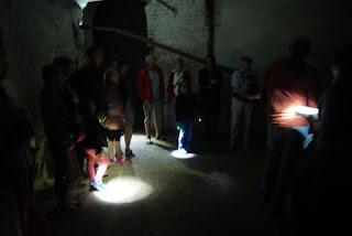 Personen im Inneren eines dunklen Raumes, der nur von Taschenlampen erleuchtet wird