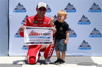 Kyle Larson, driver of the #42 Target Chevrolet, and his son, Owen, pose with the Coors Light Pole Award after qualifying for the Monster Energy NASCAR Cup Series Toyota/Save Mart 350 at Sonoma Raceway