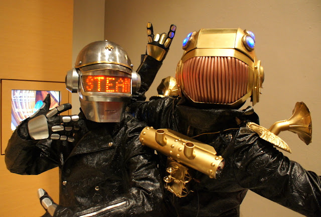 Steampunk Daft Punk Cosplay. LED light up helmets in silver and gold metal. Gloves, coats, viola horn epaulets