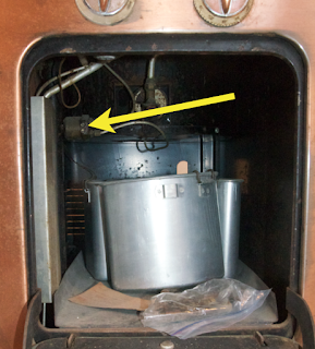 Arrow points to the pilot filter assembly inside the service cabinet of a Chambers model C and D stove