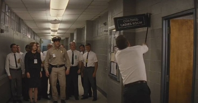 Kevin Costner tears down a segregated bathroom sign in a fictional scene from Hidden Figures (2016).