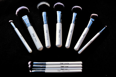 A selection of white make up brushes, spread out on a black background.