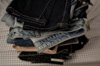 Pile of folded Denim Jeans, clothing on a bed