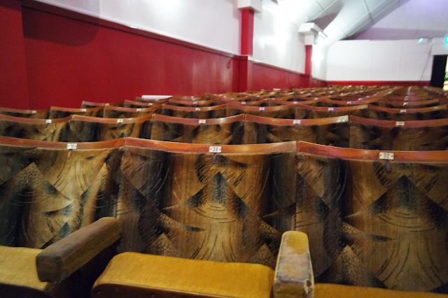 rows of empty wooden seats in North Pier theatre