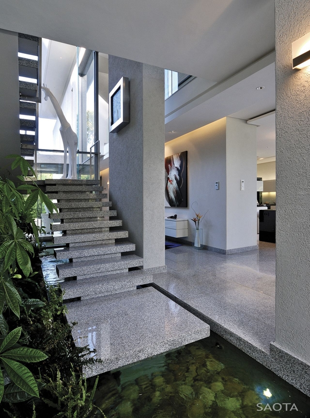 Picture of modern marble staircase with vegetation and small pond on the ground floor